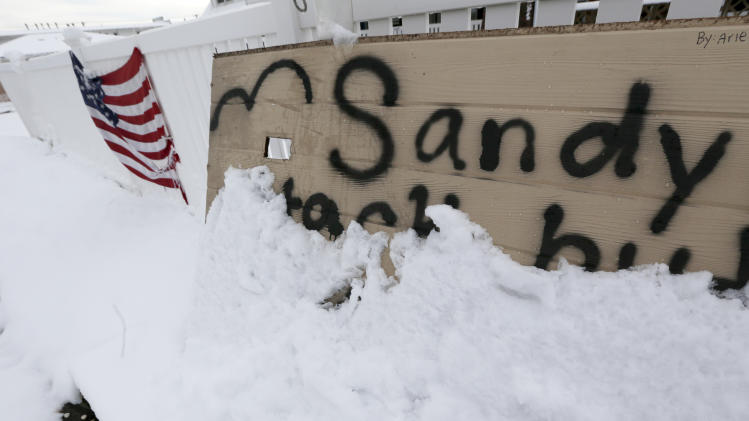 A message about Superstorm Sandy on a wooden board is half covered by snow the morning after a nor'easter rolled through the already damaged beachfront town of Point Pleasant, N.J., Thursday, Nov. 8, 2012. (AP Photo/Julio Cortez)