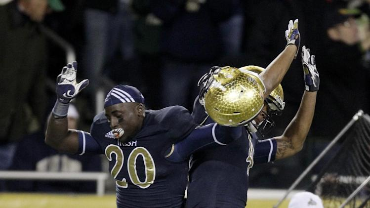 Notre Dame running back Cierre Wood (20) and running back George Atkinson III, celebrate Woods touchdown during the second half of an NCAA college football game against Miami at Soldier Field Saturday, Oct. 6, 2012, in Chicago. (AP Photo/Nam Y. Huh)