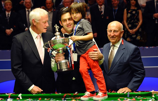 Ronnie O'Sullivan (2nd L)of England and his son Ronnie Jr. celebrate on May 7, 2012 with the chairman of World Snooker, Barry Hearn (L), and sponsor Fred Done (R) after beating Ali Carter of England 1