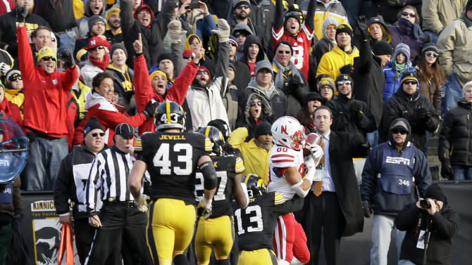 Nebraska wide receiver Kenny Bell (80) catches a 9-yard touchdown pass in front of Iowa defensive back Greg Mabin (13) during overtime in an NCAA college football game, Friday, Nov. 28, 2014, in Iowa City, Iowa. Nebraska won 37-34 in overtime. (AP Photo/Charlie Neibergall)