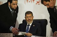 Egyptian President Mohammed Morsi (centre) attends the 12th summit of the Organisation of Islamic Cooperation in Cairo, on February 6, 2013. Morsi has urged Syrian opposition groups to unify, as he addressed leaders of Islamic states at a summit that also tackled the battle against militants in Mali