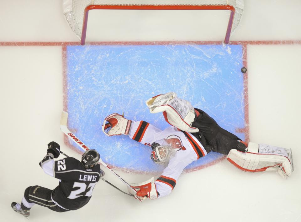 New Jersey Devils' goalie Martin Brodeur makes a save as Los Angeles Kings' Trevor Lewis appraoches in the third period during Game 4 of the NHL hockey Stanley Cup finals, Wednesday, June 6, 2012, in Los Angeles. The Devils won the game 3-1.  (AP Photo/Mark Terrill)