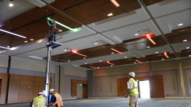 This April 12, 2013, photo shows workers installing colored lighting in the Music City Center in Nashville, Tenn. Nashville's new convention center is transforming the look of downtown with its wavy roof dominating six city blocks, but tourism officials hope the eye-catching facility will also show business travelers a revitalized Music City. (A P Photo/Mark Humphrey)