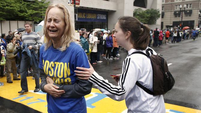 Pam Vingsness, right, comforts her crying mother, Rachel, of Newton, Mass., after they crossed the finish line, as runners who were unable to finish the Boston Marathon on April 15 because of the bombings were allowed to finish the last mile of the race in Boston, Saturday, May 25, 2013. (AP Photo/Winslow Townson)
