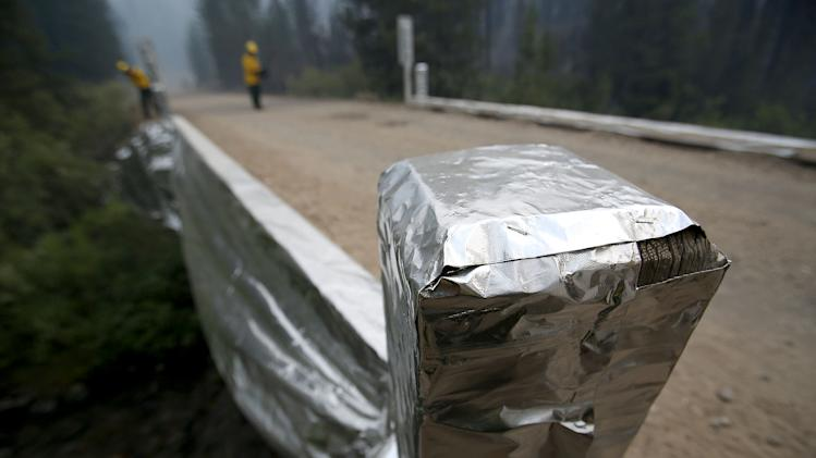 In this Monday, Aug. 19, 2013 photo, bridges over Baker Creek have been wrapped in aluminum foil to protect them from the 104,457-acre Beaver Creek Fire in the Baker Creek area, north of Ketchum, Idaho. (AP Photo/Times-News, Ashley Smith)