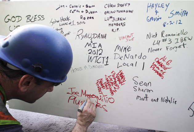 "FILE- In this Aug. 2, 2012 file photo, a construction worker signs a ceremonial steel beam at One World Trade Center in New York. The beam was signed by President Barack Obama with the notes: ""We reme"
