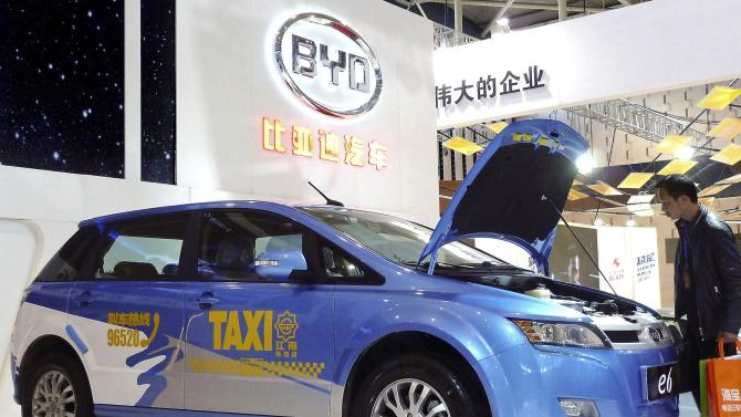 File photo of a visitor looking at a BYD E6 electric car on display at the New Energy Auto Expo in Nanjing
