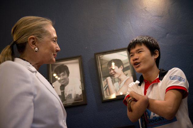 U.S. Secretary of State Hillary Rodham Clinton, left, greets Phongsavath Souliyalat, who lost his forearms and sight from a blast of an unexploded bomb left since Vietnam War while she tours the Coope