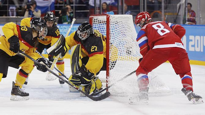 Iya Govrilova of Russia scores a goal past Goalkeeper Viona Harrer and Tanja Eisenschmid,left, of Germany during the third period of the 2014 Winter Olympics women's ice hockey game at Shayba Arena, Sunday, Feb. 9, 2014, in Sochi, Russia. AP Photo/Petr David Josek)