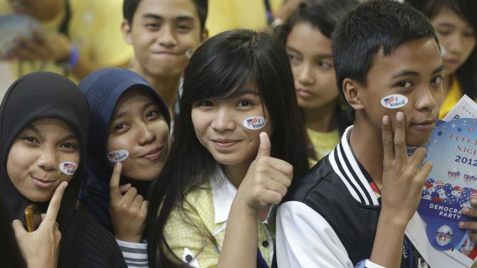 """Muslim students pose before a throng of photographers shortly after """"voting"""" in the mock U.S. election at a shopping mall at suburban Quezon city, northeast of Manila, Philippines Wednesday, Nov. 7, 2012. Filipinos participated in a mock U.S. elections between President Barack Obama and Republican challenger Mitt Romney which was organized by the U.S. Embassy in Manila. (AP Photo/Bullit Marquez)"""