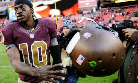 "Washington Redskins quarterback Robert Griffin III tosses his helmet after losing on Nov. 4, a result that could be bad news for Obama, according to a piece of superstition known as the ""Redskins Rule."""