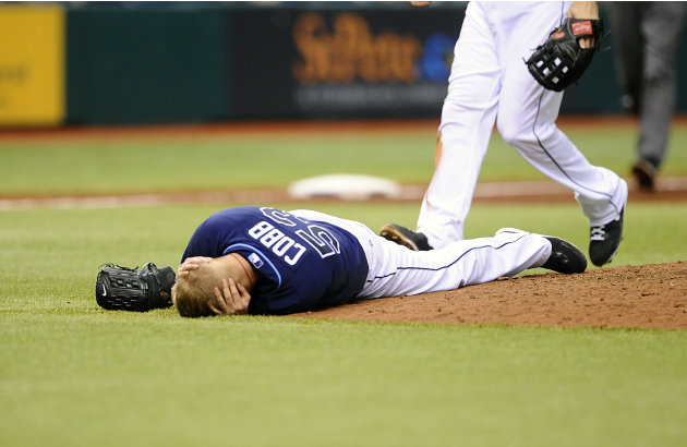 Tampa Bay Rays starting pitcher Alex Cobb grabs his head and lies on the pitcher's mound after being hit by a line drive by Kansas City Royals' Eric Hosmer during the fifth inning of a baseball game S