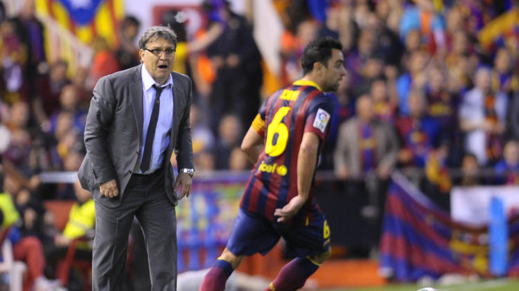 Barcelona's coach Gerardo Martino of;;owe the action from the side line during the final of the Copa del Rey between FC Barcelona and Real Madrid at the Mestalla stadium in Valencia, Spain, Wednesday, April 16, 2014. (AP Photo/Manu Fernandez)