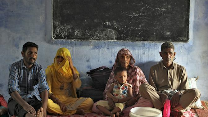 Villagers sit inside a relief camp after they evacuated from their village near the border with Pakistan in Akhnoor