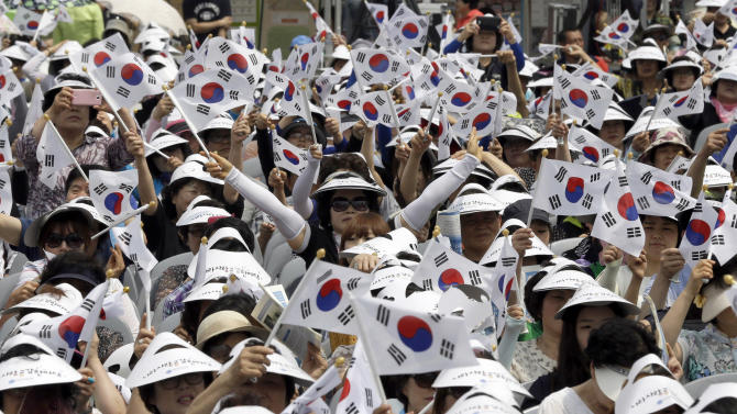 Members of Korea Freedom Federation wave their national flags during a ceremony to mark the 63rd anniversary of the outbreak of the Korean War in Seoul, South Korea, Tuesday, June 25, 2013. The three-year Korean War broke out on June 25, 1950, when Soviet tank-led North Koreans invaded South Korea. (AP Photo/Lee Jin-man)
