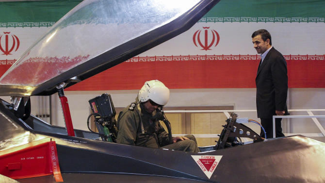 FILE-- In this file photo taken on Saturday, Feb. 2, 2013, Iranian President Mahmoud Ahmadinejad, right, makes his way during a ceremony to unveil Iran's newest fighter jet, Qaher-313, or Dominant-313, as an unidentified pilot sits into the aircraft, in Tehran, Iran.  (AP Photo/Fars News Agency, Hossein Zohrevand,File)