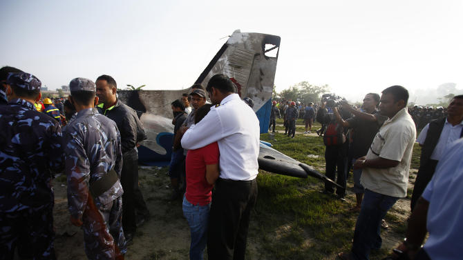 A Nepalese relative of a crew member is comforted at the crash site of a Sita Air airplane near Katmandu, Nepal, early Friday, Sept. 28, 2012.  The plane carrying trekkers into the Everest region crashed just after takeoff Friday morning in Nepal's capital, killing all 19 people on board, authorities said. (AP Photo/Niranjan Shrestha)