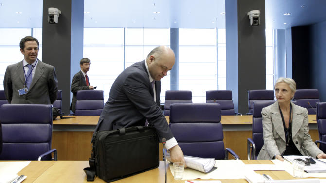 Greek Finance Minister Georgios Zanias, center, takes his papers out of his bag during a meeting of eurozone finance ministers in Luxembourg on Thursday, June 21, 2012. As the cracks in the euro currency seem to grow even wider, finance ministers from the 17 countries that use the currency brainstorm Thursday on how to stabilize it. (AP Photo/Virginia Mayo)