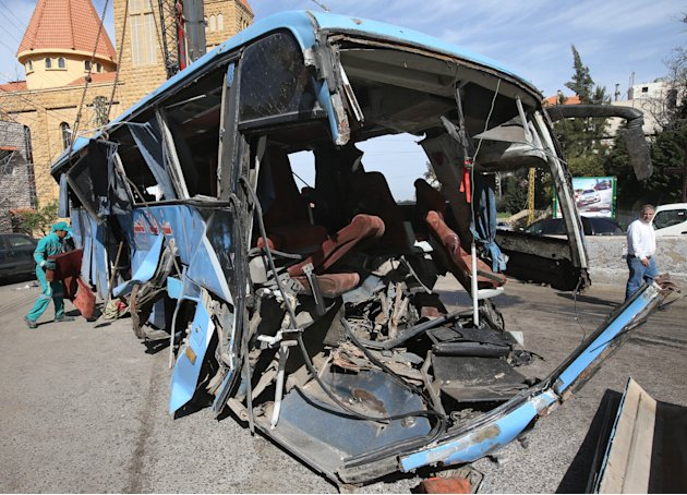 A worker, left, removes a damaged seat from a destroyed Syrian bus that was headed to the Lebanese capital, Beirut, when an accident occurred in the Kahhaleh region of Lebanon, Friday March 15, 2013.