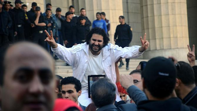 Prominent Egyptian blogger Alaa Abdel-Fattah is surrounded by supporters after his release from detention in Cairo, Egypt, Tuesday, March 26, 2013. Abdel-Fattah after refusing to cooperate with prosecutors into accusations he instigated violence against the country's most powerful Islamist group through comments posted on social media. Abdel-Fattah handed himself in to authorities earlier Tuesday, a day after the country's prosecutor general ordered his arrest along with four others opposition figures on the same charges. (AP Photo/ Mostafa Darwish)
