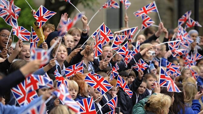 This image made available by LOCOG shows local schoolchildren waving Union Jack flags as they cheer on the Torchbearers in Wakefield, England during Day 38 of the London 2012 Olympic Torch Relay Monday June 25, 2012. (AP Photo/Ben Birchall/LOCOG) The Torchbearer's name is provided in good faith, however the Press Association has been unable to verify it independently.