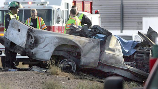 Emergency personnel are next to a burned truck that was traveling east in the the west bound lanes of Interstate 10 and struck a tour bus Tuseday Nov. 20, 2012 in Casa Grande, Ariz. The driver of the truck was killed, two people were flown to Phoenix hospitals and six were transported to Casa Grande Regional Medical Center. The collision is under investigation by Arizona Department of Public Safety Highway Patrol.(AP Photo/Casa Grande Dispatch, Oscar Perez)