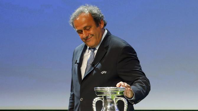 UEFA President Platini touches the trophy after the announcement of the 13 cities which will host matches at the Euro 2020 tournament to be played across the continent, during a ceremony in Geneva