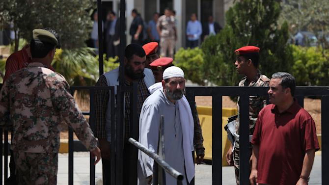 Omar Othman, center, the father of radical Muslim preacher Abu Qatada, waits in front of the Jordanian military court in Amman, Jordan, Sunday, July 7, 2013. A Jordanian military prosecutor says he has charged a radical Muslim preacher with conspiring to carry out al-Qaida-linked attacks on Americans, Israelis and other Westerners in this key U.S. ally. Abu Qatada, 53, arrived in Jordan earlier Sunday after being deported from Britain. (AP Photo/Mohammad Hannon)