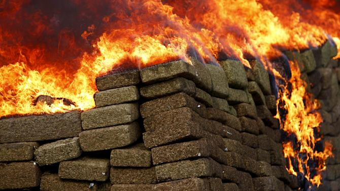 A pile of marijuana is being incinerated at a camp of the Mexican Army's 28th infantry battalion in Tijuana