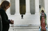 A person prays during a protest in front of the US Supreme Court, on April 25, 2012 in Washington, DC. The US Supreme Court struck down most of Arizona's new immigration law but let stand a key provision requiring police spot-checks that critics say amount to racial profiling
