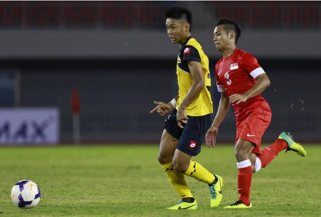 Mohammad Sahil Suhaimi of Singapore and Mohammad Kahri Shame Suhami of Brunei fight for ball during their soccer match at the 27th SEA Games in Naypyitaw