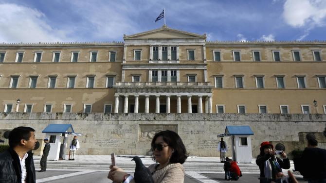 Tourists take pictures in front of the Greek parliament in Athens