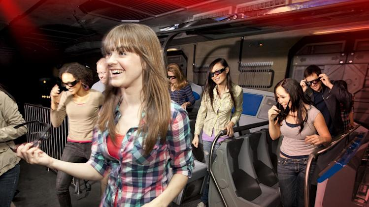 "In this undated image released by Universal Studios Hollywood, riders exit the ""Transformers the Ride: 3D,"" attraction at Universal Studios Hollywood in Los Angeles. Debuting May 25 at Universal Studios Hollywood, the ride, based on the film franchise, offers motion-simulator vehicles and 3D high definition video. (AP Photo/Universal Studios Hollywood)"