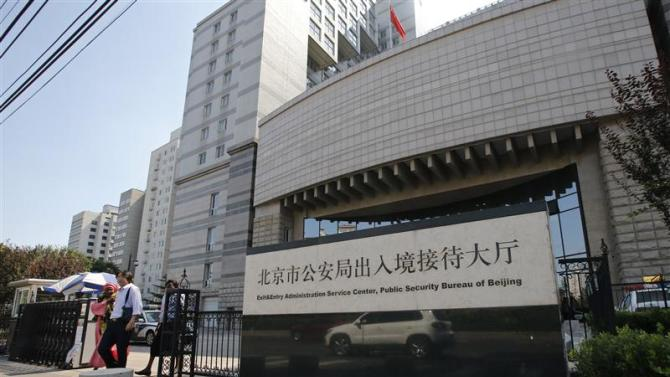 Foreigners walk out from Beijing's Exit & Entry Administration Service Center