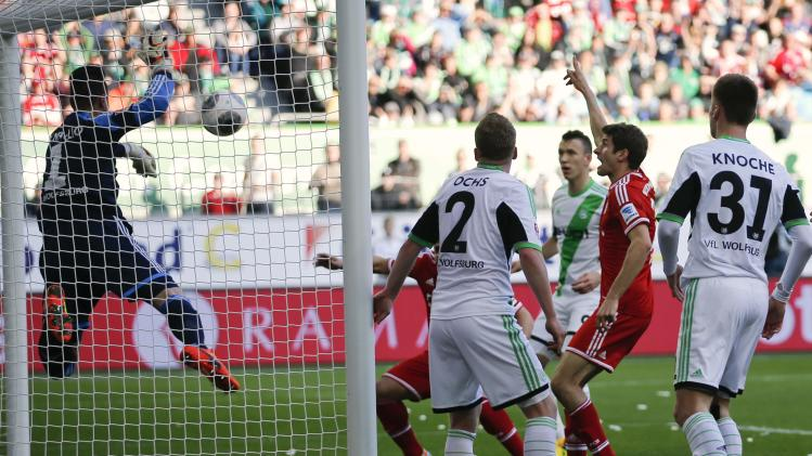 Bayern's Mueller celebrates after he scores a goal against Wolfsburg goalkeeper Benaglio during their German first division Bundesliga soccer match in Wolfsburg