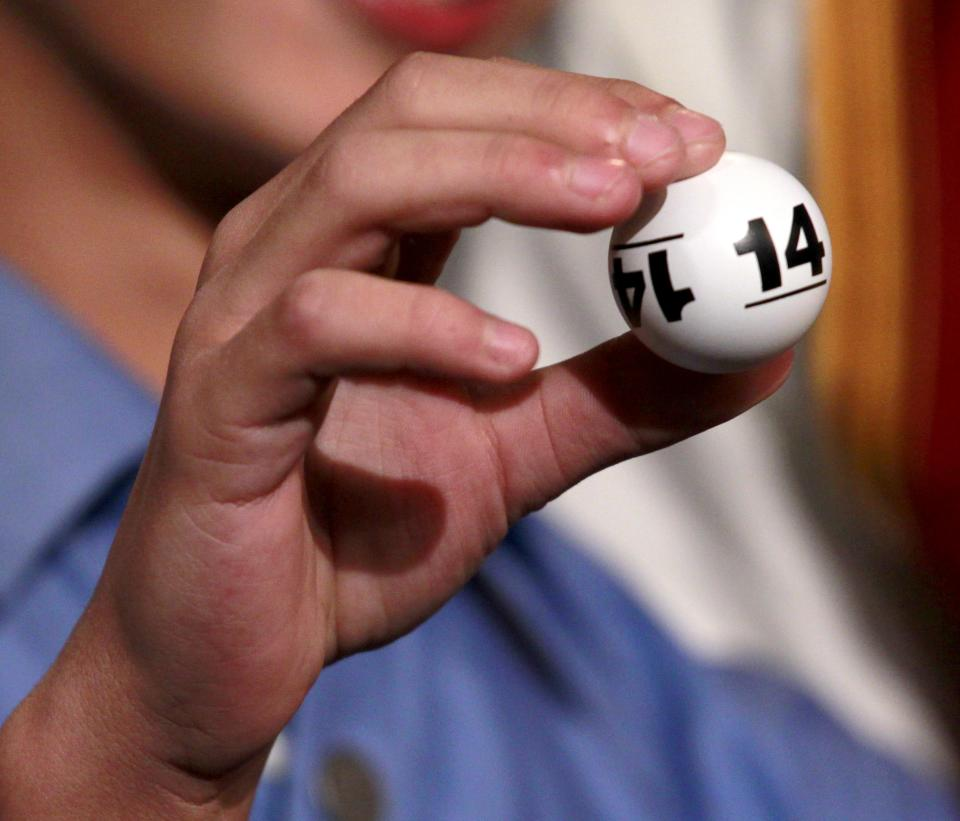 Grant Gilbert, 13, the son of Cleveland Cavaliers owner Dan Gilbert, holds one of the lottery numbers that were drawn in combination giving the Cavaliers first place during the 2011 NBA basketball draft lottery, Tuesday, May 17, 2011 in Secaucus, N.J. (AP Photo/Julio Cortez)