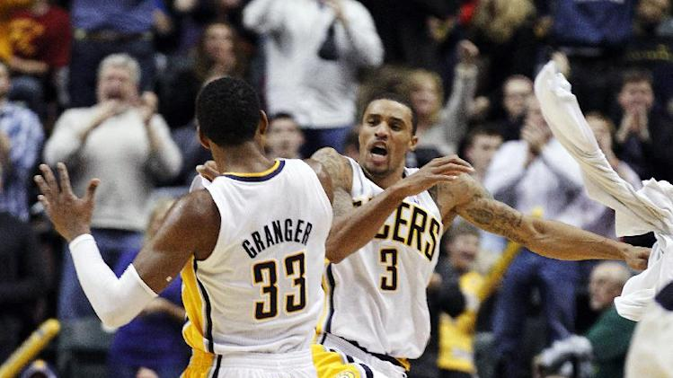 Indiana Pacers forward Danny Granger, left, and guard George Hill celebrate after Granger scored during the overtime period of an NBA basketball game against the Cleveland Cavaliers in Indianapolis, Friday, Dec. 30, 2011. The Pacers won 98-91 in overtime. (AP Photo/Michael Conroy)