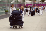 French Olympians high-jumper Melanie Skotnik, left, and Marlene Harnois who won a bronze medal in the Taekwondo women's -57kg category, push luggage as they leave the athlete's village to board a train after the 2012 Summer Olympics in London, Monday, Aug. 13, 2012. (AP Photo/Matt Dunham)