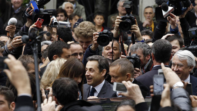 French President and UMP candidate Nicolas Sarkozy, center, is greeted by supporters as he leaves with his wife Carla Bruni-Sarkozy after casting his vote in the second round of French presidential elections in Paris, France, Sunday, May 6, 2012.  (AP Photo/Remy de la Mauviniere)