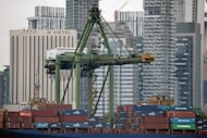 <p>This file photo shows a vessel loaded with cargo containers, sitting anchored along the wharf of Keppel port in Singapore. The city-state on Friday cut its growth forecast for this year again after the economy shrank more sharply than expected in the third quarter as exports were hit by a slump in global demand.</p>