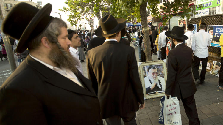 File - In this Oct. 13, 2013 file photo, ultra-Orthodox Jewish men walk past a picture of the late religious spiritual leader of Israel's Sephardic Jews, Rabbi Ovadia Yosef, at a ceremony a week after his funeral in Jerusalem. The Spanish conservative government, which enjoys an absolute majority in Parliament, plans to make amends in weeks to come with a law that offers citizenship to the legions of Jews forced to flee Spain in 1492. (AP Photo/Sebastian Scheiner, File)