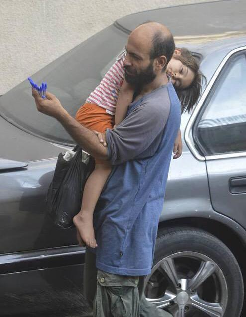 Story Behind Emotional Photo of Refugee Dad Carrying Sleeping Daughter