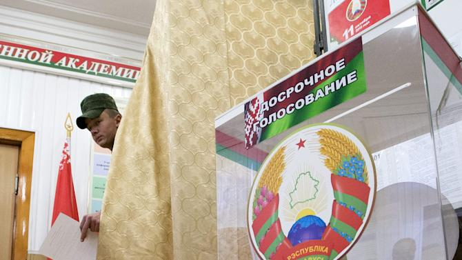 Belarussian cadet leaves a voting booth to cast his ballot during pre-schedule voting at a polling station in Minsk