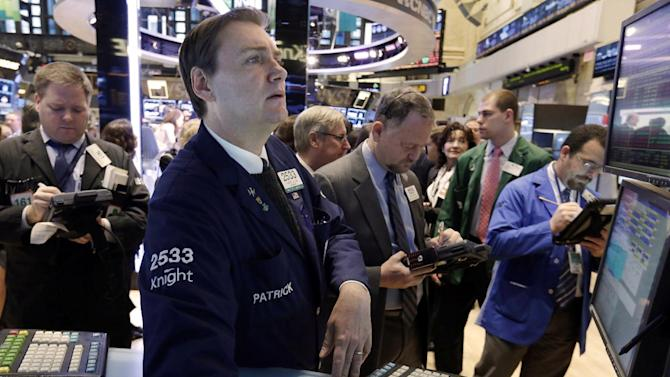Specialist Patrick King, second left, works on the floor of the New York Stock Exchange Tuesday, Jan. 8, 2013. U.S. stocks opened mostly lower Tuesday as traders awaited the start of U.S. corporate earnings season. (AP Photo/Richard Drew)