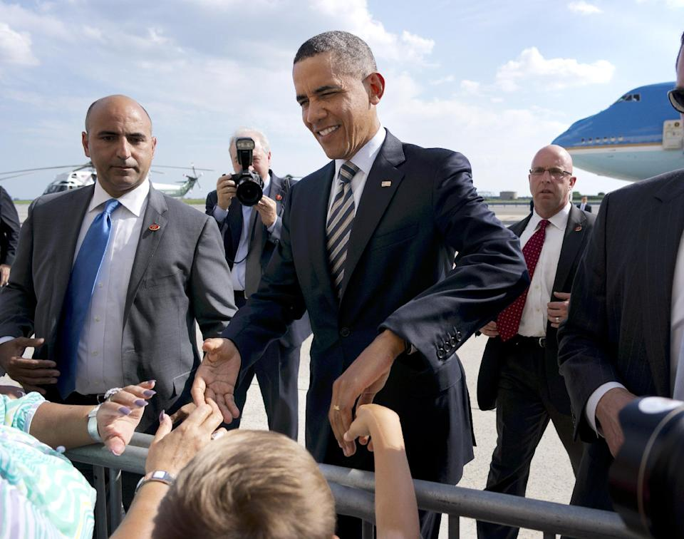 President Barack Obama greets visitors on the tarmac upon his arrival at JFK International Airport on Air Force One in New York, Monday, Aug., 6, 2012. Obama is campaigning in Connecticut for a pair of fundraisers tonight. (AP Photo/Pablo Martinez Monsivais)