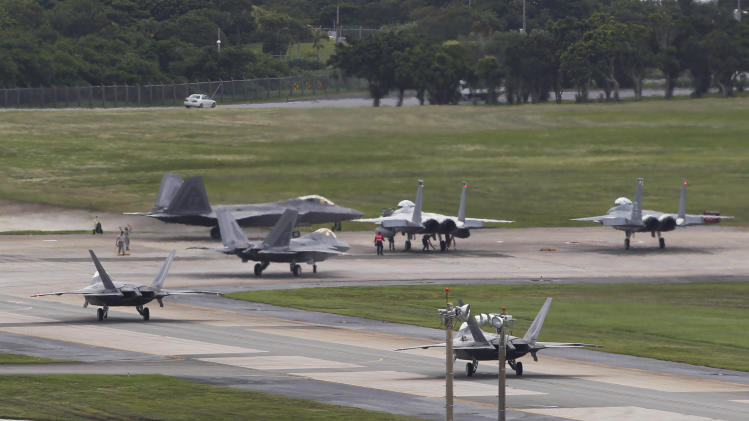 In this Aug. 14, 2012 photo,  U.S. Air Force F-22 Raptor stealth fighters, left, and two F-15 fighters prepare for take-off at Kadena Air Base on the southern island of Okinawa, in Japan. The U.S. is hoping a dozen F-22 stealth fighters now roaring through the skies of southern Japan will prove its most prized combat aircraft is finally ready to resume full operations after years of investigations into why its pilots were getting dizzy and disoriented. But questions remain over whether the Air Force has taken enough action to fix a potentially bigger problem - the shriveling of programs to test cockpit life support systems after nearly 20 years of budget cuts, downsizing and outsourcing. (AP Photo/Greg Baker)