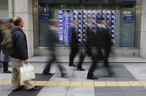 A man looks at a stock quotation board as passers-by walk past, outside a brokerage in Tokyo December 4, 2013. REUTERS/Toru Hanai