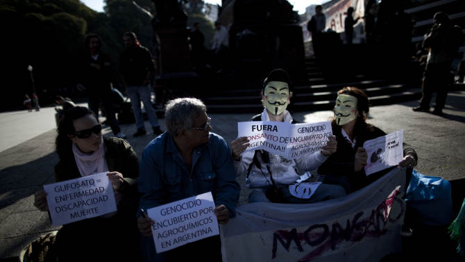 """Demonstrators hold signs reading in Spanish """"Glyphosate = illness, disability, death,"""" left, """"Genocide concealed by agrochemicals in Argentina,"""" second from left, and """"Get out Monsanto from Argentina"""" near the offices of the U.S.-based company Monsanto in Buenos Aires, Argentina, Saturday, May 25, 2013. Activists are taking part in a global protest """"March Against Monsanto"""" against the seed giant, demanding a stop to the use of agrochemicals and the production of genetically modified food. Protesters say genetically modified organisms can lead to serious health conditions and harm the environment. (AP Photo/Natacha Pisarenko)"""
