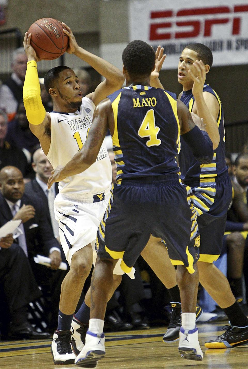 Marquette's Todd Mayo (4) and Juan Anderson, right, pressure West Virginia's Gary Browne (14) in the first half of an NCAA college basketball game, Friday, Feb. 24, 2012, in Morgantown, W.Va. (AP Photo/David Smith)