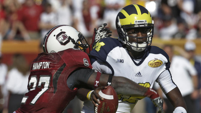 Michigan quarterback Devin Gardner (12) is sacked by South Carolina cornerback Victor Hampton (27) during the second quarter of the Outback Bowl NCAA college football game, Tuesday, Jan. 1, 2013, in Tampa, Fla. (AP Photo/Chris O'Meara)